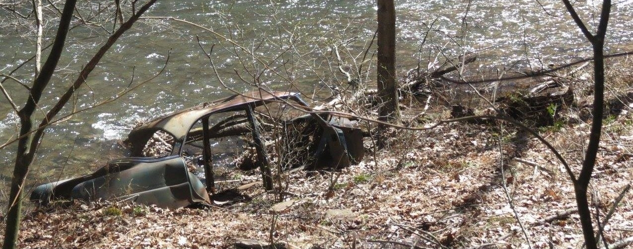 Old car seen in water off embankment at Young Woman's Creek.